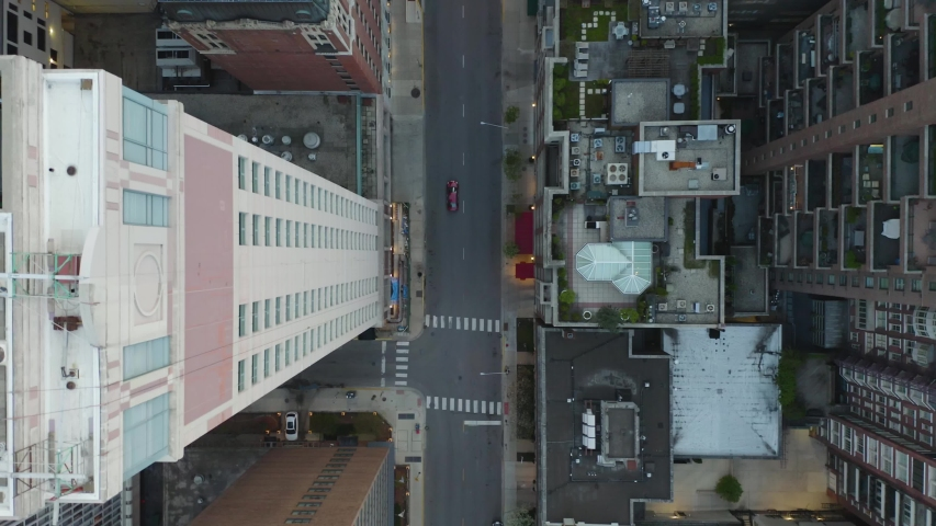 Red Car Drives between Skyscrapers on Empty One Way Street, Birds Eye Aerial | Shutterstock HD Video #1052233825