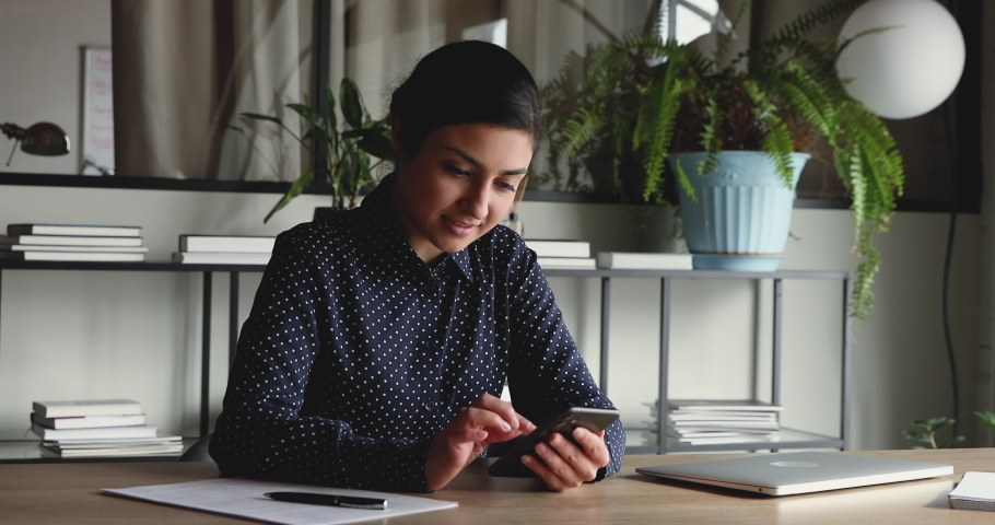 Professional indian businesswoman holding modern smart phone texting message in office. Young female employee using modern mobile technology business app, typing email on cell sitting at work desk. Royalty-Free Stock Footage #1052235208