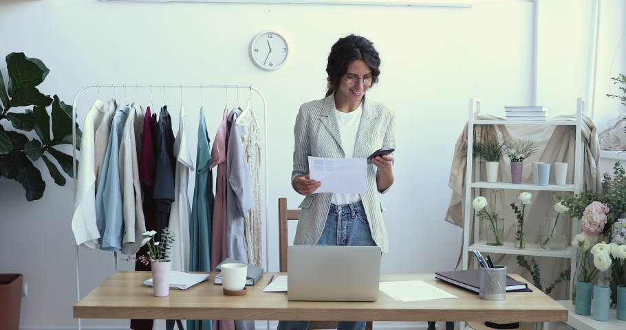 Smiling young female fashion designer stylist holding swatches palette using smart phone at workplace, texting message, communicating with customer, taking clothing online atelier order in cell app. Royalty-Free Stock Footage #1052240332