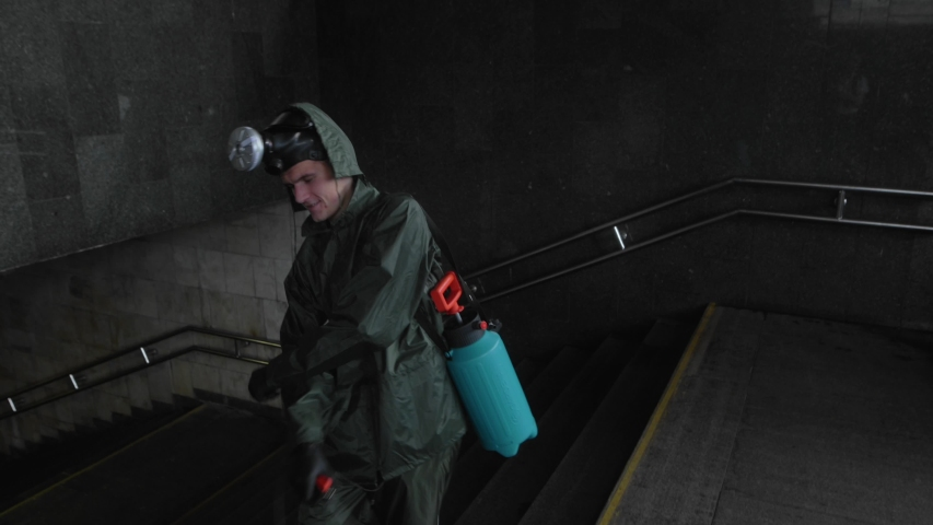 Kyiv, Ukraine - May 2, 2020.Funny young man in a protective suit and with a gas mask on his head, sprays a disinfectant and smiles looking into the camera. C   Shutterstock HD Video #1052262610