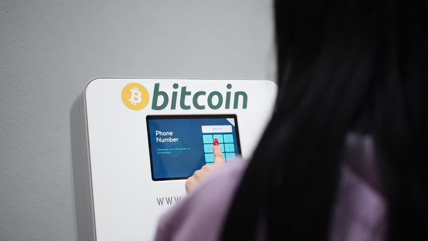 Woman making a withdrawal from the bitcoin ATM machine in HD VIDEO. Cryptocurrency technology in real life concept. Close-up. Royalty-Free Stock Footage #1052280334