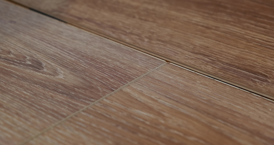 Close-up of laying laminate on prepared substrate, wooden floor, lock joining, male builder works on laying floor, precise joining of joints, hand in frame, dirty nails, hands of working person | Shutterstock HD Video #1052296294