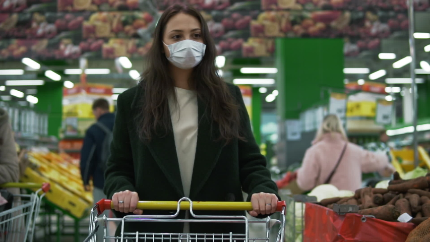 Young woman wearing protective medical face mask rolls shopping cart at grocery store. Female customer picks vegetables at economy supermarket during covid-19 coronavirus pandemic, social distancing | Shutterstock HD Video #1052297536