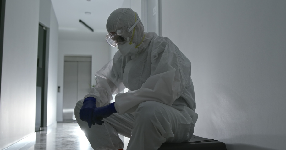 Tired male health worker with face bruises take off protective uniform after overwork with patients COVID 19 infected and then resting in corridor of modern hospital Royalty-Free Stock Footage #1052303692
