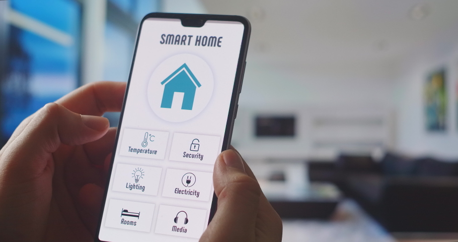 Smart home, application on the phone. A man manages various parameters of his home from a smartphone. Smart home. Man holding phone with app smart home on screen in room house