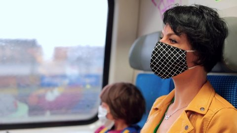 Mom and son in face masks are sitting in commuter train. Public transport place of transmission of infection. Pensive look - threat of unemployment. Using public transport is environmentally friendly.