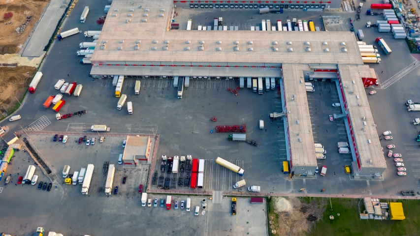 Aerial hyper lapse (hyperlapse - time lapse) of a large logistics park with a warehouse - loading hub. Semi-trucks with freight trailers standing at the ramps for loading/unloading goods  | Shutterstock HD Video #1052323507