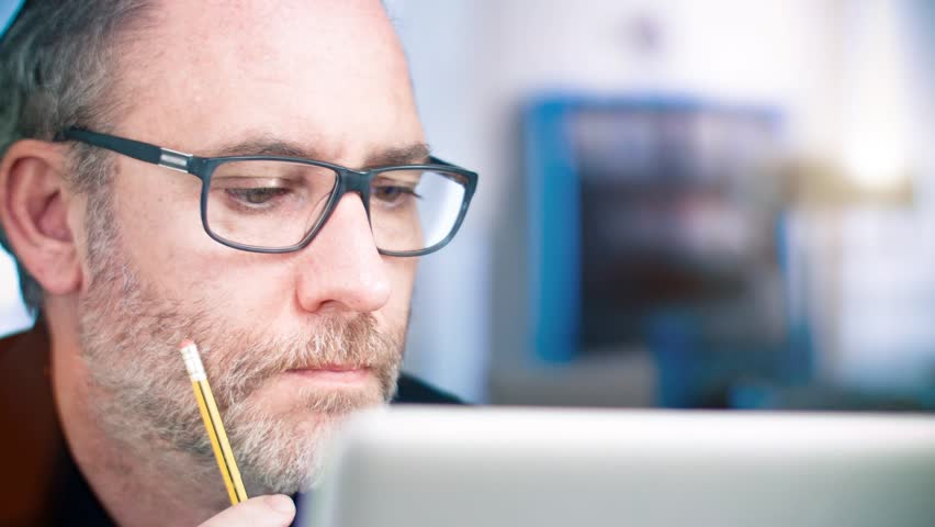 Man with glasses working on laptop computer | Shutterstock HD Video #10523411