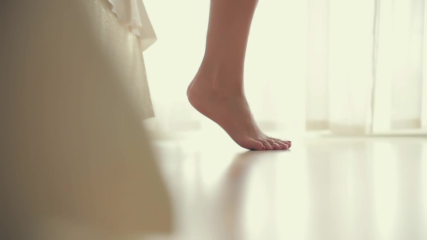 close-up shooting. legs of a pretty girl getting out of bed against the window. light background, morning wakes up. white bed beautiful female toes. go on the floor. parquet or laminate. fitness legs	 Royalty-Free Stock Footage #1052344285