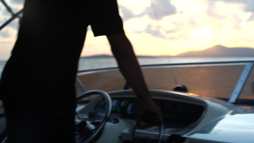 A man drives a motor boat, a yacht against the backdrop of the rising sun on the horizon, only hands and a helm are visible   Shutterstock HD Video #1052352565