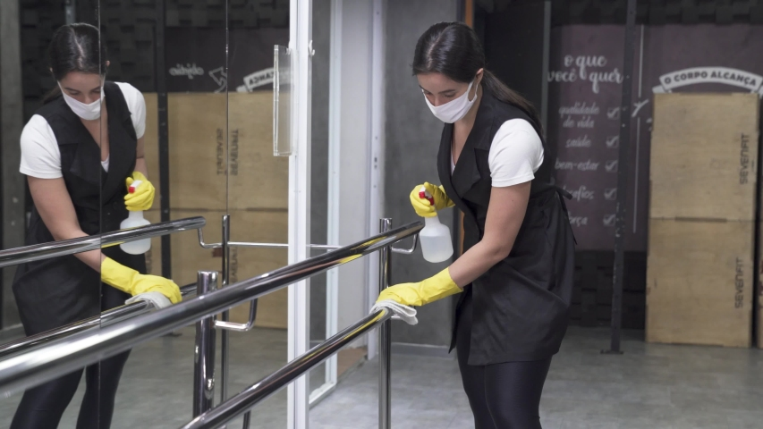 woman worker disinfects gym fitness equipment from coronavirus covid-19 with antibacterial sanitizer sprayer on quarantine. Cleaner in protective mask cleans training apparatus at workout area.  Royalty-Free Stock Footage #1052358463