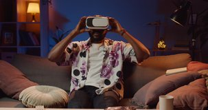 Young afro american man wearing virtual reality glasses and lookling around room. Handsome guy sitting on sofa and using vr headset while spending free time at home. Concept of tech.