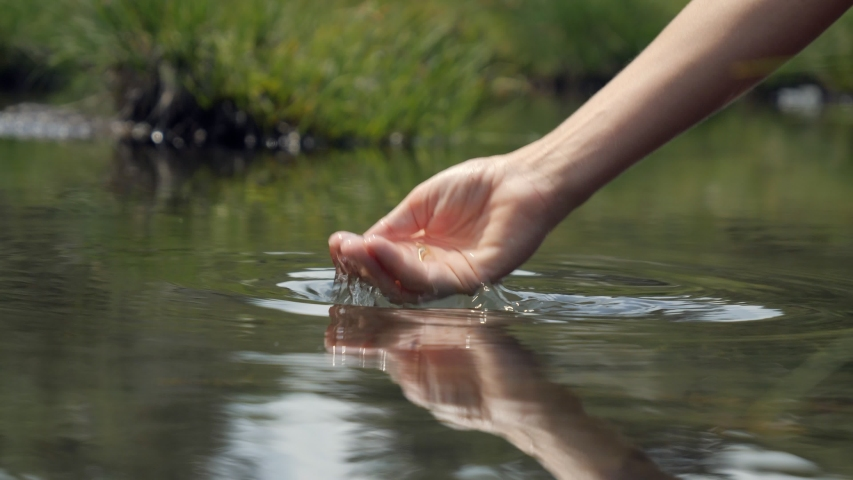 Human hand cupped to catch the fresh water from the lake, pure clean nature. Body care healthy natural. Slow motion   | Shutterstock HD Video #1052363461