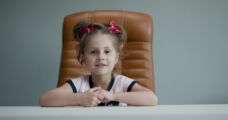 Funny Little Girl Smiling Looking at Camera at Home. Cute kid talking to webcam making online video call or recording vlog having fun. Preschool child with pretty face waving hand sitting on chair Royalty-Free Stock Footage #1052365081