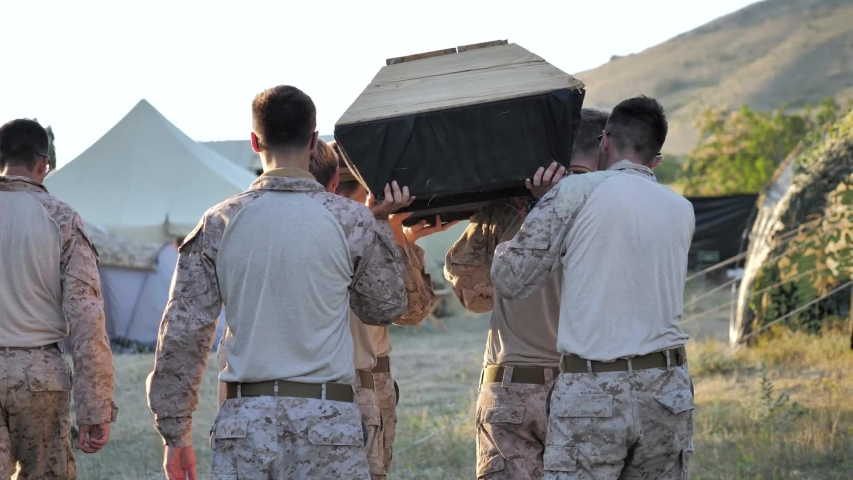 Airsoft. Military camp. Funeral of a friend. The coffin is carried on the shoulders of soldiers.