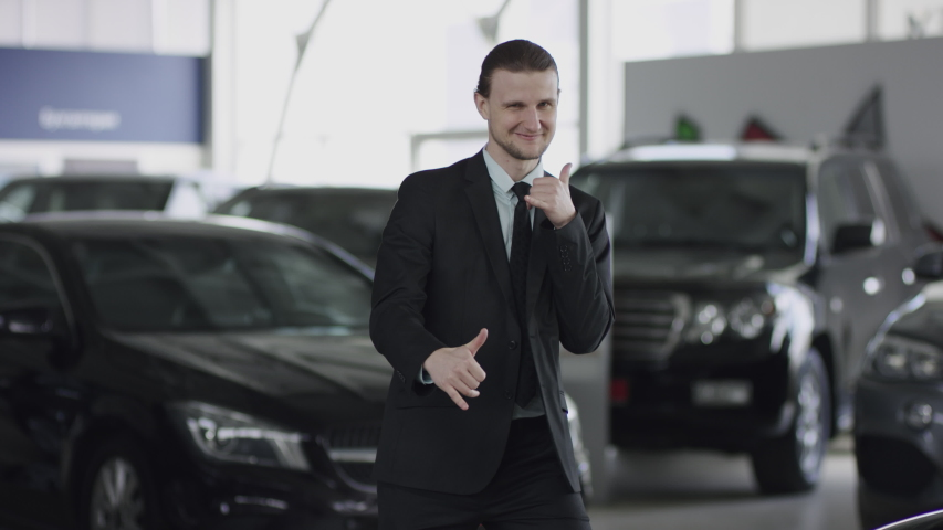 Standing between new cars in auto dealership man is giving thumb-up and posing in car showroom. He shows thumb-up looking at camera and smiling.