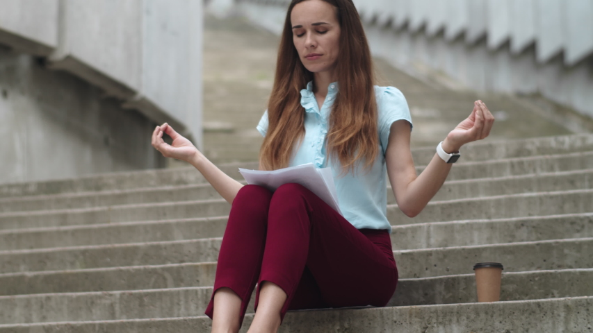 Disappointed businesswoman sitting on stairs with business papers. Tired female professional meditating on city street. Stressed business woman hands showing gyan mudra outdoors. Woman taking break | Shutterstock HD Video #1052389405