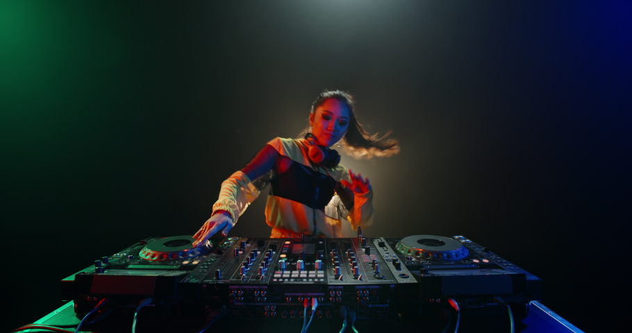 Cool female asian dj is working in a nightclub, standing at turntables, creating a dance music set - nightlife concept 4k footage | Shutterstock HD Video #1052395807