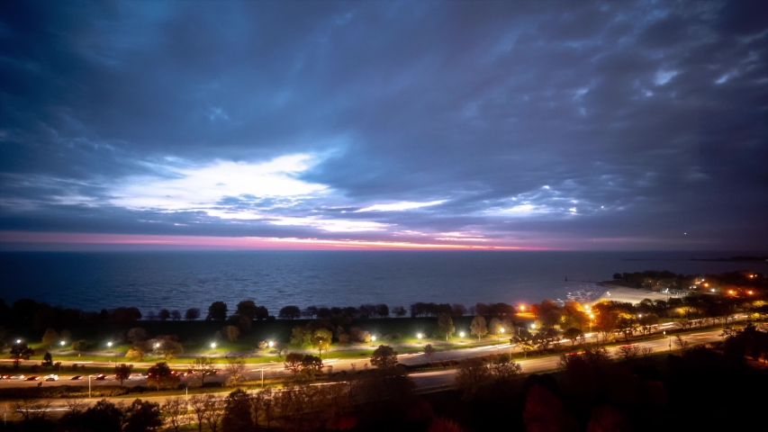 A beautiful pastel pink blue and purple sky sunrise timelapse over Lake Michigan as clouds roll overhead and traffic builds on Lake Shore Drive below.