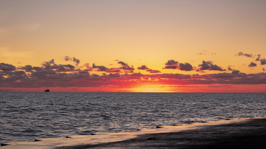 A beautiful zoom in panoramic orange and yellow sunrise timelapse over the water of Lake Michigan as the sun rises towards clouds just above the horizon as a flock of geese swim by.