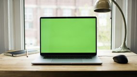 Green screen laptop computer sitting on a home work desk next to a desk lamp. Footage shot with RED, available in 4K and HD. Download the preview for free.