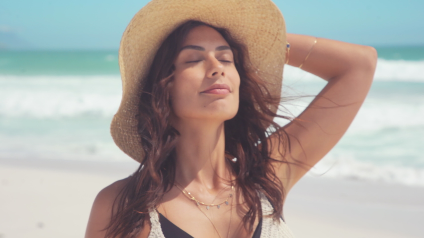 Beautiful girl with straw hat enjoying sunbath at beach. Close up face of young tanned woman with closed eyes enjoying breeze at seaside. Carefree latin woman smiling with ocean in background. Royalty-Free Stock Footage #1052406388