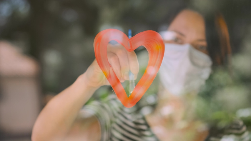 Woman painting heart on glass during isolation, illness, coronavirus Covid-19 quarantine. Young beautiful woman in medical mask drawing red heart on window at home. Stay home. Social media campaign. Royalty-Free Stock Footage #1052409085