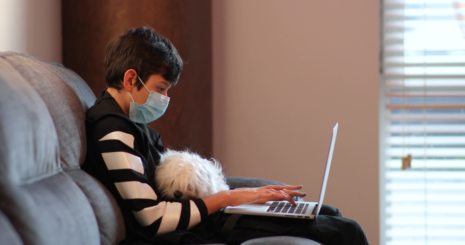 Guy in a medical mask with a white little dog in his arms sits in a room on the couch and uses a laptop. guy in quarantine communicates with friends online. Self isolation. Royalty-Free Stock Footage #1052413750