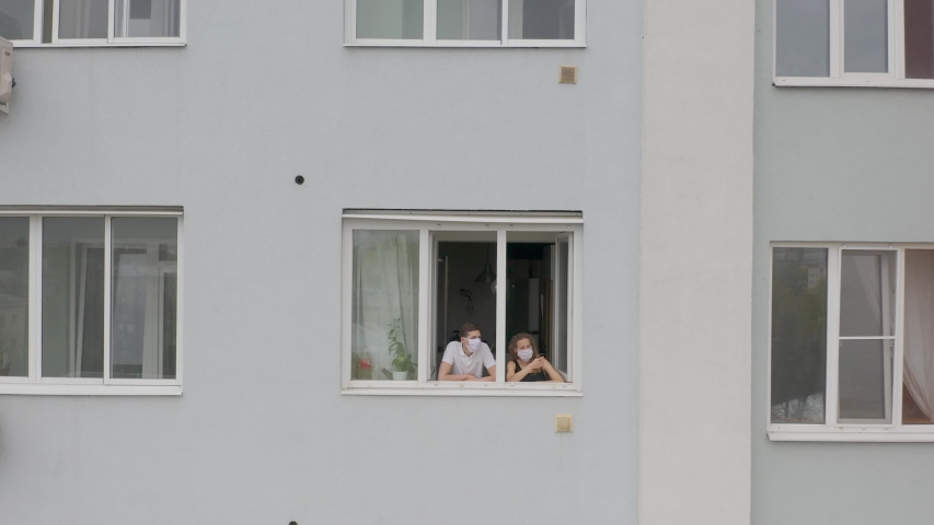 A young family of a man and a masked woman look out the window, stay at home in quarantine during pandemic. Aerial, camera move out | Shutterstock HD Video #1052415181
