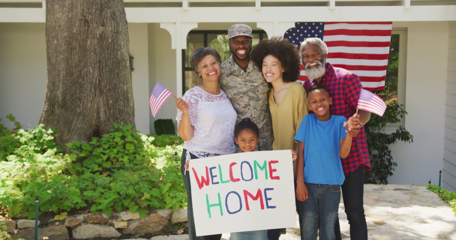 Multi-generation mixed race family enjoying their time at a garden, welcoming a mixed race man wearing military uniform, returning home, holding a sign, looking at the camera, in slow motion