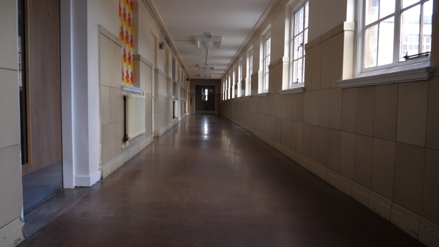 4K: Empty School or College Corridor with no people. The Long hallway is deserted in this place of eductation. Low Tracking Shot. Stock Video Clip Footage Royalty-Free Stock Footage #1052436538