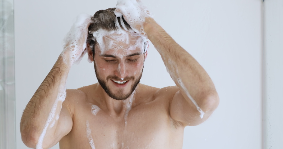 Young handsome bare man washing head with anti-dandruff shampoo lathering hair with foam. Attractive naked guy taking shower doing everyday fresh clean male haircare hygiene routine concept.