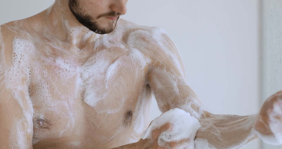 Young adult sexy bare caucasian man washing body with gel foam holding sponge puff taking shower in bathroom enjoying everyday hygiene routine for fresh clean skin care concept. Close up view