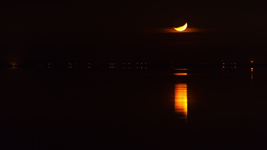 Lockdown time lapse shot of moonset with reflection in sea at night - Crescent Beach, Canada Royalty-Free Stock Footage #1052445916