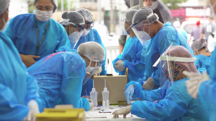 Santos / Brazil 2020 - Staff Covid-19 doctors in the PPE protective and coronavirus patients work and test at a drive thru clinic. Face masks and hand sanitizer shown.