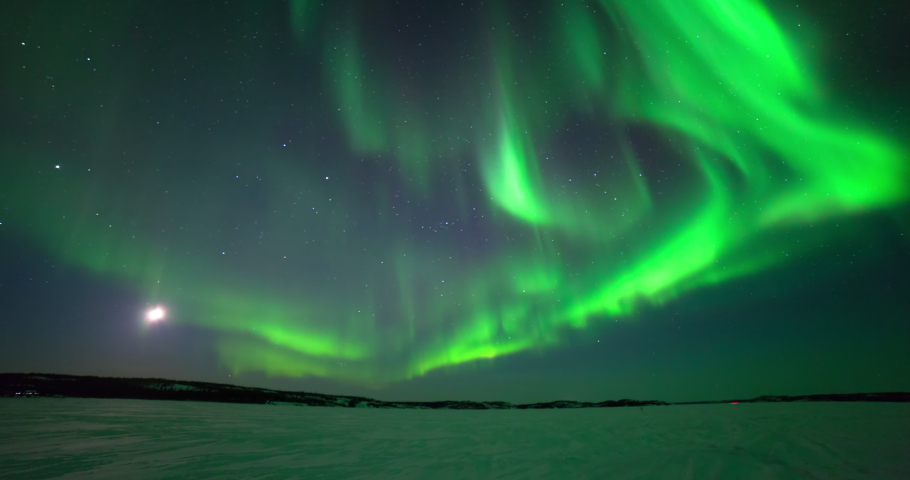 Time lapse shot of green natural lights over snow covered landscape in dark at night - Northwest Territories, Canada Royalty-Free Stock Footage #1052452108