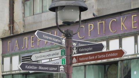BELGRADE, SERBIA - CIRCA 2020: Directional signpost in Knez Mihailova street showing directions to the landmarks of Belgrade, the Serbian capital city