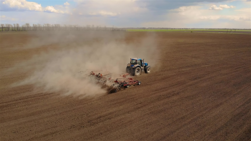 Aerial footage of modern blue tractor with red plough plowing or cultivating large field. Spring agronomic activity on agricultural land | Shutterstock HD Video #1052452900