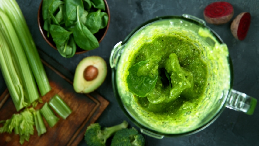 Green fresh smoothie blended in blender, top view. Healthy eating concept. Super slow motion filmed on high speed cinematic camera.   Shutterstock HD Video #1052453617