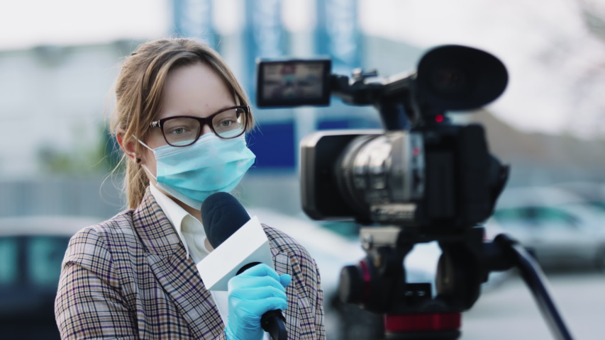 Newscaster presenting the breaking news, during COVID-19 pandemic. Female reporter with medical mask speaking into microphone. | Shutterstock HD Video #1052467006