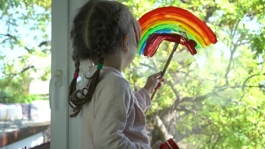 A child draws a rainbow on the glass of a balcony. Colourful rainbow pictures drawings on windowsspread hope during coronavirus pandemic. Covid-19 outbreak. Home lockdown Royalty-Free Stock Footage #1052468626