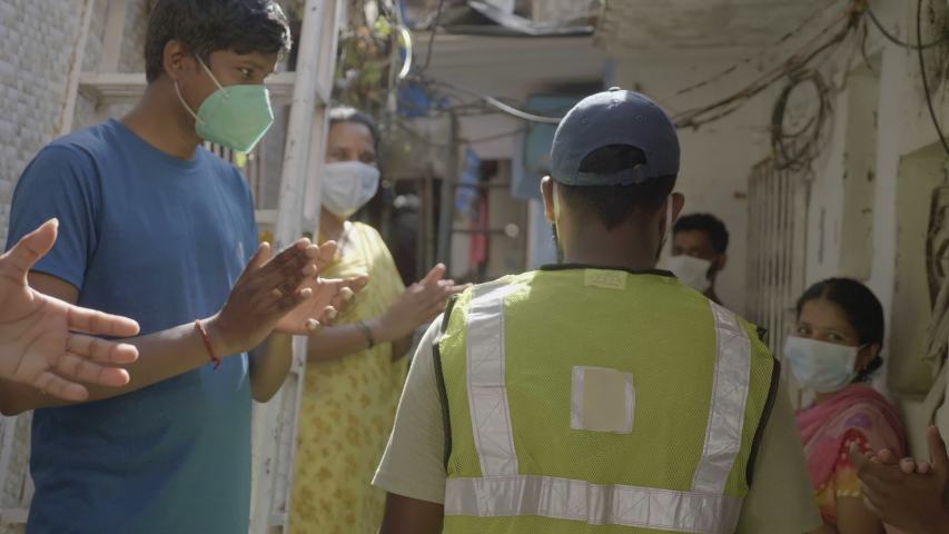 People men and women wearing protective face masks are outside their houses and clapping claps when health worker essential service provider doctor passing through a lane, Mumbai, India (May 2020)