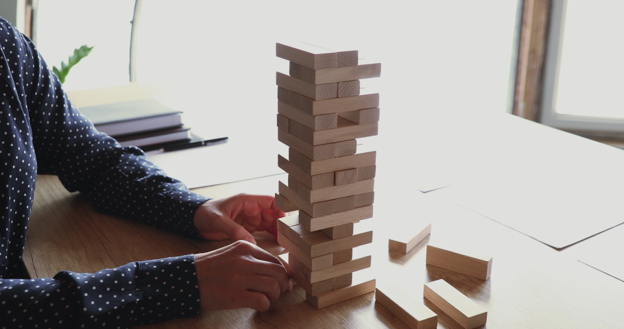 Female hands taking wooden bricks out of tower falling down playing build game on office desk. Bad risk management, choice mistake, wrong decision, business strategy failure concept. Closeup view Royalty-Free Stock Footage #1052489992
