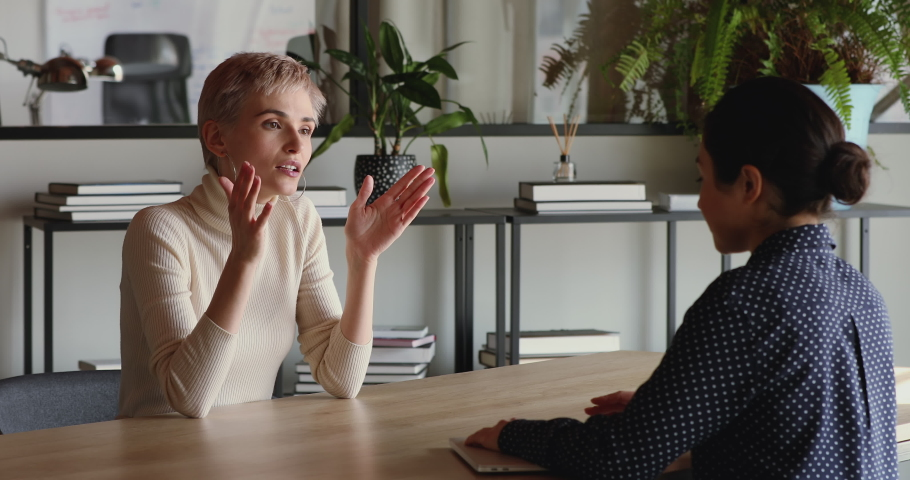 Confident young business woman vacancy candidate negotiating with employer, company recruiter at employment interview. Competent qualified female job applicant answering hr questions sitting at table. Royalty-Free Stock Footage #1052490028