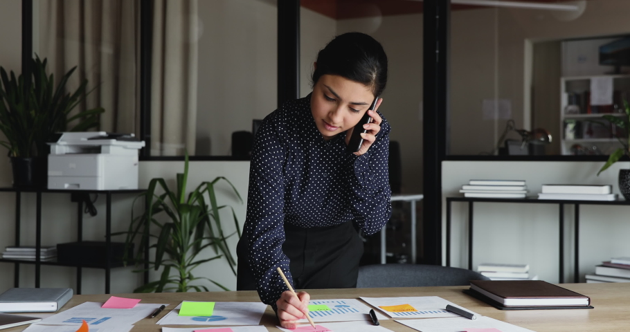 Young busy indian business woman working on project paperwork talking on the phone. Ethnic female manager making business call on mobile writing tasks on sticky notes working alone in office. Royalty-Free Stock Footage #1052490031