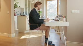 Funny Clip: Businessman Wearing Jacket and No Pants Uses Laptop and Conference Video Call Software App for a Board of Directors Online Meeting. Remote Work, Work at Home, Home Office Concept.Side View