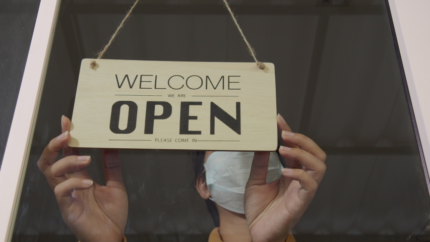 Asian woman wear mask turning Welcome we are open sign on fronton glass door store. Reopening activity after COVID-19, ended the lockdown and quarantine. Restarting again and keep forward concept Royalty-Free Stock Footage #1052506894
