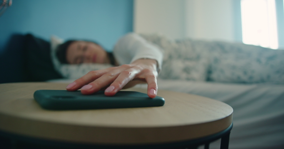 Beautiful Girl Sleeping in Bed at Home Wakes Up to Turn off Alarm Clock Triggered on Her Smartphone and Goes Back to Sleep Covering up in Blanket. No Need to Wake up Early in Morning. Slow Motion Shot Royalty-Free Stock Footage #1052507917