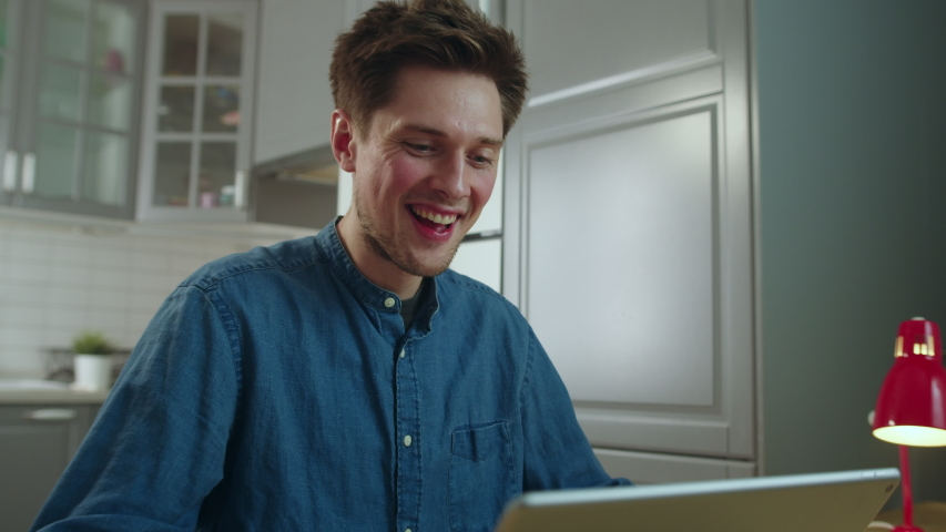 Side View of Young Man Sitting at Table in Kitchen, Making Video Call Using Tablet. Handsome Guy Waving Hello to Friends, Family, Video Chatting, Smiling and Laughing. Slow Motion Cinematic Shot | Shutterstock HD Video #1052508067