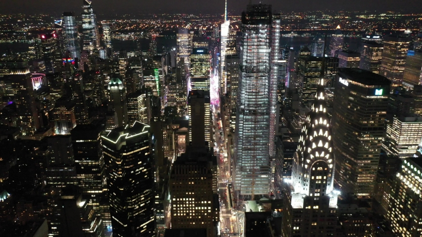 NEW YORK - CIRCA 2020 - An aerial view shows the skyline of 42nd Street in New York City, New York at night, highlighting the Chrysler Building.